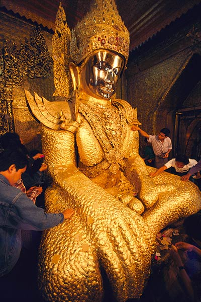 Pilgrims applying gold leaf to the Maha Muni Buddha Mandalay, Burma