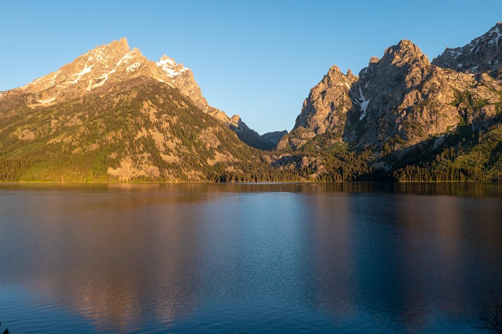 La première lumière du soleil du matin sur Symmetry Spire et le mont Saint John sur le lac Jenny, Grand Tetons, Wyoming