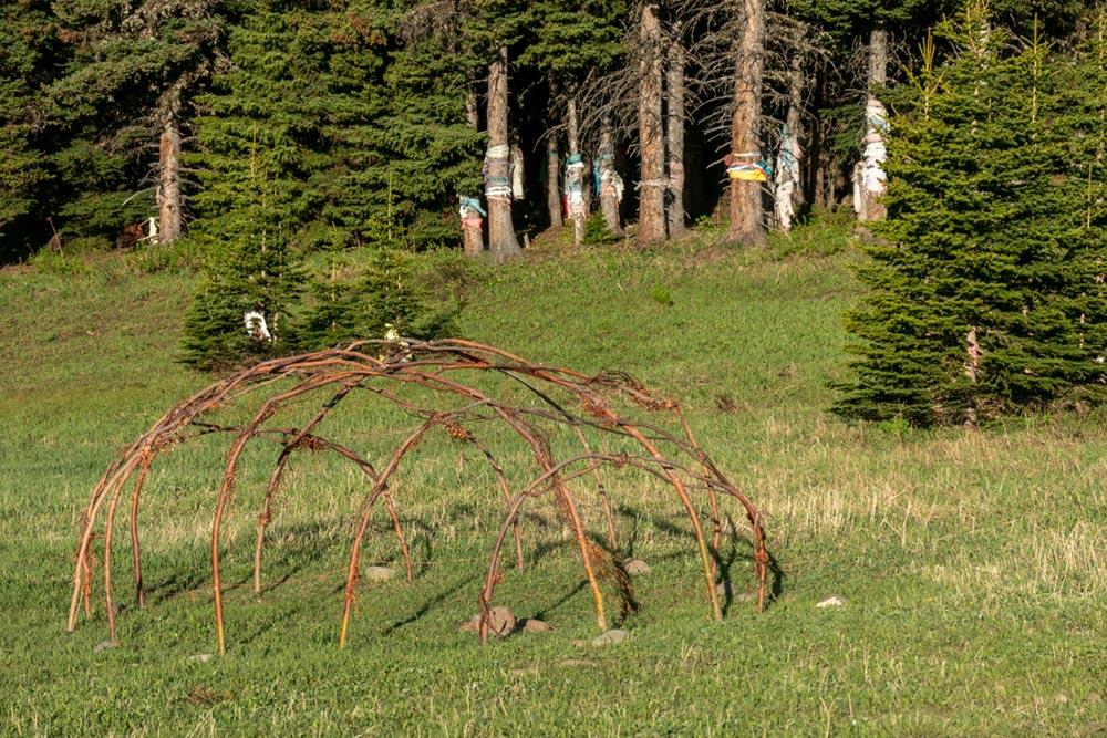 Cadre en bois de la suerie amérindienne et marquages de prière en tissu sur les arbres, Chief Mountain