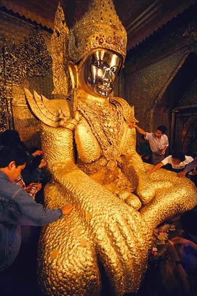 Паломники, применяющие сусальное золото к Маха Муни Будда Мандалай, Бирма