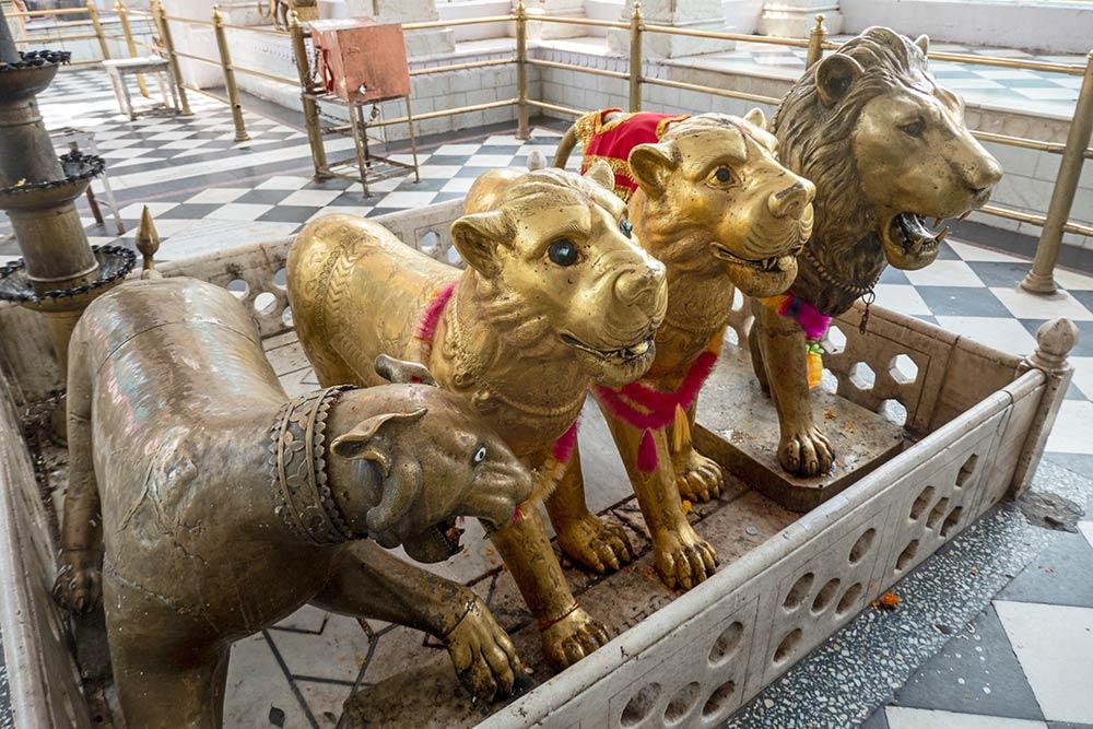 Esculturas en metal de leones en la entrada del templo Brajeshwari Devi Shakti Peetha, Kangra