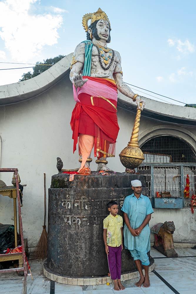 Pellegrini in posa per la fotografia con la statua di Hanuman, Chamunda Devi Mandir